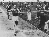 Los Angeles 1932: Poland's Janusz Kusocinski breaks through the finishing tape during the 10,000m final and wins the gold medal with a time of 30:11.4 minutes.
