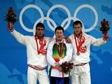 (L-R) Silver medalist Dmitriy Klokov of Russia, gold medalist Andrei Aramnau of Belarus and Dmitry Lapikov of Russia stand on the podium during the medal ceremony the men's 105kg group weightlifting event.
