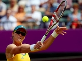 LONDON, ENGLAND - JULY 28:  Samantha Stosur of Australia returns a shot against Carla Suarez Navarro of Spain during her Women's Singles Tennis match on Day 1 of the London 2012 Olympic Games at the All England Lawn Tennis and Croquet Club in Wimbledon on July 28, 2012 in London, England.