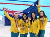 (L-R) Melanie Schlanger, Alicia Coutts, Brittany Elmslie and Cate Campbell celebrate with their gold medalis and their counrty's flag  during the medal cermony for the Women's 4x100m Freestyle Relay on Day 1 of the London 2012 Olympic Games at the Aquatics Centre on July 28, 2012 in London, England.