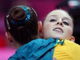 Lauren Mitchell of Australia hugs a teammate after competing on the beam in the Artistic Gymnastics Women's Team qualification on Day 2 of the London 2012 Olympic Games at North Greenwich Arena on July 29, 2012 in London, England.