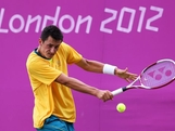 LONDON, ENGLAND - JULY 29:  Bernard Tomic of Australia plays a backhand during the Men's Singles Tennis match against Kei Nishikori of Japan  on Day 2 of the London 2012 Olympic Games at the All England Lawn Tennis and Croquet Club in Wimbledon on July 29, 2012 in London, England.