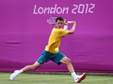 Bernard Tomic plays a backhand during the Men's Singles Tennis match against Kei Nishikori of Japan  on Day 2 of the London 2012 Olympic Games at the All England Lawn Tennis and Croquet Club in Wimbledon on July 29, 2012 in London, England.
