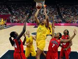Liz Cambage (C) shoots over Maya Moore (R) and Tina Charles of the USA during the London 2012 Olympic Games women's semifinal basketball game bewteen Australia and the USA on Day 13 of the London 2012 Olympics Games at North Greenwich Arena on August 9, 2012 in London, England.