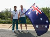 Lauren Jackson of the Australian Women's basketball team poses with closing cermony flag bearer, gold medallist sailor Malcolm Page (L) during an Australian flag handover at the Olympic Park Common Domain on Day 16