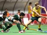 Pakistan's Muhammad Usman Aslam and Muhammad Sultan Amir tries to steal the ball away from Australia's Daniel Beale in the Pakistan versus Australia boys' preliminary hockey match of the Singapore 2010 Youth Olympic Games.
