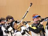 Korean shooter Kim Yong (centre with rifle pointing into the air) prepares to fire on his target during the 10m air rifle men's juniors final competition of the Singapore 2010 Youth Olympic Games.
