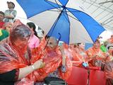 Spectators take cover from the torrential rain that hit the Australia v Chile hockey match.