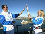 Torchbearer Zali Steggall (R) passes the Olympic Flame to Kieren Perkins atop the Sydney Harbour Bridge during the Athens 2004 Olympic Torch Relay in Sydney, Australia. The Olympic Flame travelled to 34 cities in 27 countries en route to the Athens 2004 Olympic Games.