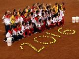 Silver medallists from the United States, gold medallists from Japan and bronze medallists from Australia pose for a group photo behind the year 2016 spelled out in softballs (signifying their desire to reinstate softball as an Olympic sport since it will not be during the 2012 Olympic summer games) during the medal ceremony after USA lost 3-1 to Japan during the women's grand final gold medal softball game.