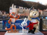 A tourist poses for a photograph in front of the official mascots prior to the Sochi 2014 Winter Olympics at the Rosa Khutor Mountain village cluster on February 1, 2014 in Sochi, Russia.