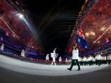 Snowboarder Alex Pullin of the Australia Olympic team carries his country's flag during the Opening Ceremony of the Sochi 2014 Winter Olympics.