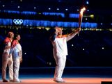 Russian former wrestler Alexander Karelin holds up the Olympic torch next to Russian pole vaulter Yelena Isinbayeva (2nd L) and Russian tennis player Maria Sharapova (L) during the opening ceremony of the Sochi 2014 Winter Olympics at the Fisht Olympic Stadium on February 7, 2014.