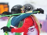 Sanna Luedi (R) of Switzerland celebrates with Katya Crema in the Freestyle Skiing Womens' Ski Cross 1/8 Finals on day 14 of the 2014 Winter Olympics.