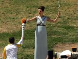 Actress Katerina Lehou who plays the role of high priestess passes the olympic flame to the first torchbearer and reigning world champion gymnast Lefteris Petrounias during the Lighting Ceremony of the Olympic Flame for the Rio Olympic Games on April 21, 2016 in Olympia, Greece.
