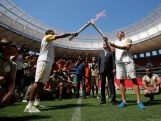 Brazilian former footballer Lucio (r) and Brasilia's governor Rodrigo Rollemberg receive the Olympic flame from fireman Haudson Alves at the field of the Brasilia National Stadium during the torch in Brasilia during the Olympic Flame torch relay on May 3, 2016 in Brasilia, Brazil.