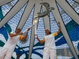 Former Marathon runner Vanderlei Cordeiro passes the Olympic Torch to Paula Pequeno in Cathedral of Brasilia during the Olympic Flame torch relay on May 3, 2016 in Brasilia, Brazil.