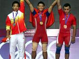 Gold medallist Thach Kim Tuan (centre) of Vietnam, silver medallist Xie Jiawu (left) of China and bronze medallist Smbat Margaryan (right) of Armenia pose during the victory ceremony for the men's 56kg weightlifting competition.