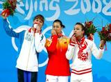 (L-R) Silver medal winner Alla Vazhenina of Kazakhstan, gold medal winner Cao Lei of China and bronze medal winner Nadezda Evstyukhina of Russia kiss their medals on the podium during the medal ceremony for the women's 75kg weightlifting.