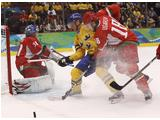 Aleksei Ugarov #18 of Belarus battles for the puck with Patric Hornqvist #27 of 