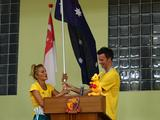 Chef de Mission Nick Green passes on the Flag Bearer honours to pole vaulter Liz Parnov at the Official Team Reception in Singapore