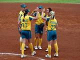 (L-R) Justine Smethurst #11 and Jodie Bowering #27 of Australia gather at the mound with the rest of the infield after recording an out against Japan during the bronze medal final of the women's softball event.