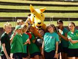Children participating in sports activities with Olympians and Paralympians pose with the Boxing Kangaroo mascot as part of celebrations marking the 10th anniversary of the Sydney 2000 Olympics