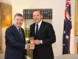 IOC President Thomas Bach presents Australian Prime Minister Tony Abbott with a special Olympic medal for heads of state during a meeting at Parliament House in Canberra on 29 April 2015.