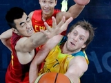 Joe Ingles  is defended by Wang Zhizhi, left, and Yi Jianlian, top, of China as he tries to score during the Men's Basketball Preliminary Round on Day 6 of the London 2012 Olympic Games at Basketball Arena.