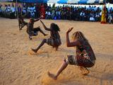 Local residnets dance during the Olympic flame ceremony at the city celebration site in Goree island in Dakar, capital of Senegal.