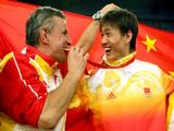 Zhong Man of China (R) smiles as his coach Christian Bauer bites his gold medal for the men's fencing individual sabre held at the Fencing Hall of National Convention Center .