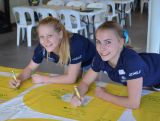 Artistic gymnasts Rianna Mizzen and Shannon Neate, at the Brisbane IGNITE session, signing the banner with a message that will be waiting for them in the Rio Olympic Village.
