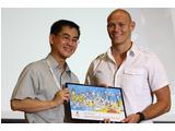 Olympian Michael Klim accepts a gift of a friendship mural for his role in the Chat with a Champion program at the Singapore 2010 Friendship Camp.