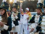 The Torch is carried alongside a marching band in the Russian town of Ivanovo.