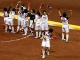 Eri Yamada #11 (bottom C) of Japan celebrates with her teammates after their 3-1 win against the United States during the women's grand final gold medal softball game.