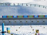 An overview of Seefeld Arena's shooting range with biathletes skiing over the top.