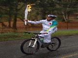 <p>Dan Scott carries the Olympic torch on his mountain bike as he leaves Fort Rodd Hill National Historic Site </p>