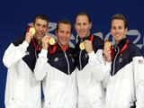 (L-R) Michael Phelps, Brendan Hansen, Jason Lezak and Aaron Piersol of the United States hold up their gold medals from the Men's 4x100 Medley Relay at the National Aquatics Centre.