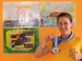 Weightlifter Tia-Clair Toomey with medals next to artwork made by Australian school kids for the Team.