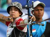 Begunhan Elif Unsal of Turkey (left) in action while her teammate, Mohamed Jaffar Bin Abdud Dayyanr of Singapore watches on during the Archery Mixed Team Bronze Medal Match. Mohamed and Unsal won 6-5.