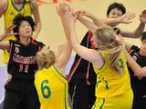 Girls from both Japan and Australia fight for a ball in a Girls' preliminary basketball match between Japan and Australia. Japan won the match 17 - 10.