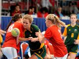 Australia's Victoria Fletcher (centre in green) attempts a shot on goal while Denmark's Rikke Ebbesen (left #18) and Camilla Madsen (right #2) attempts to block during the women's handball preliminary match