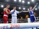 Referee annonces Michelus Dawid(R) of Poland wining the Bantam 54kg boxing bronze medal match