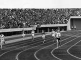 Tokyo 1964: Betty Cuthbert of Australia (No.12) crosses the finish line to win the 400m final. Ann Packer of Great Britain (left) won the silver medal.