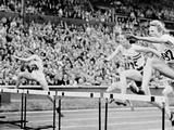 London 1948: Fanny Blankers-Koen of Holland clears a hurdle on her way to winning the women's 100m hurdles. The dark-haired athlete to her left is Maureen Gardner of Great Britain who won silver medal. At the age of 30 and after the deprivations of war, she became the world's most famous woman athlete when she won four gold medals at the London Games.  Between 1938 and 1951 she set world records in seven different events: at the 1948 Olympic Games she won gold in the 100m, 200m, 80m hurdles and the sprint relay.