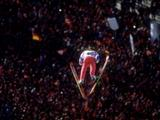 Espen Bredesen of Norway flies through the sky in the 90km ski jump in front of his home crowd and wins the gold medal.