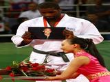 Teddy Riner of France holds up a picture as he receives the bronze medal in the men's 100 kg judo event .