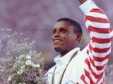 Carl Lewis of the USA celebrates on the podium after winning his third consecutive long jump crown. His jump of 8.67m defeated world record holder Mike Powell by three centimetres.