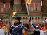 Five-time synchronised swimming Olympic Gold medallist, Anastasia Davydova (L), and three-time world champion and two-time Olympic champion in gymnastics, Svetlana Khorkina (R), hold the Olympic torches in front of St.Basil's cathedral just outside the Red Square in Moscow, on October 7, 2013, during a ceremony to kick off the Sochi 2014 Winter Olympic torch relay across Russia.