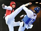 Liu Chang (L) of China kicks Yazan Alsadeq of Jordan during men's +73kg semifinal match